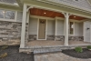 Front porch with tan door, stone and gray siding