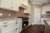 white kitchen cabinetry, walk-in pantry, built-in oven hood, gray countertop