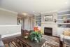 fireplace, built-ins, orange chair, designer rug, hardwood flooring, new ranch for sale pittsford
