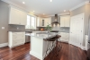 white kitchen, gray granite counters, gray walls, warm hardwood floors, wood stools, new home for sale Pittsford